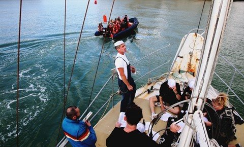 People singing sea shanties on the deck of a small yacht at sea