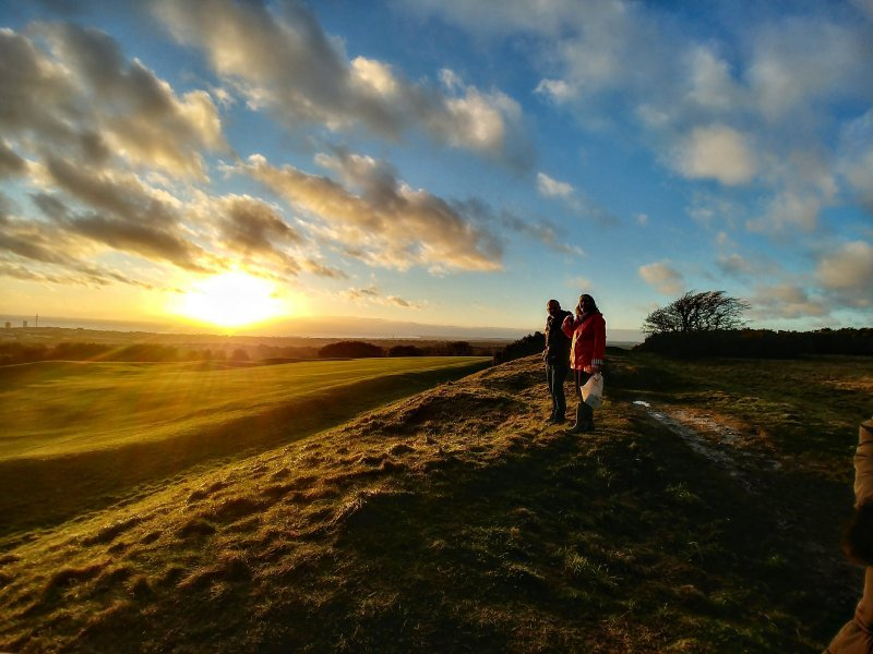 Two people standing at top of hill on the downs